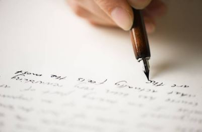 On voit un élève rédiger le commentaire de texte sur une page blanche.