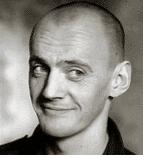 On voit un portrait de Jean-Luc Lagarce en noir et blanc qui sourit.